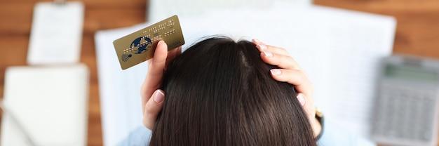 Kobieta z kredytową kartą bankową w rękach trzymających głowę widok z góry koncepcja kryzysu gospodarczego economic