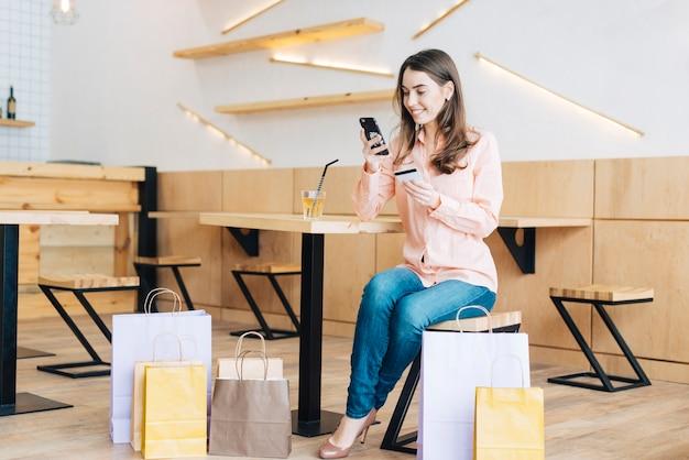 Kobieta z kredytową kartą używać smartphone w kawiarni