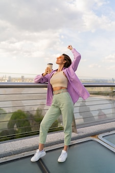 Kobieta z krótką fryzurą, chodzenie na nowoczesny most w wietrzny letni dzień