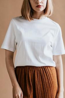 Kobieta z krótkimi, brązowymi włosami w białej koszulce i brązowej spódnicy