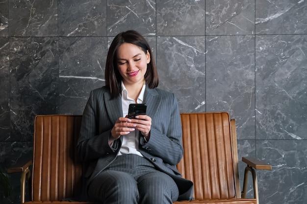 Kobieta z krótkimi ciemnymi włosami na czarnym smartfonie siedząca na brązowej ławce przed szaro-białą marmurową ścianą w nowej recepcji biurowej
