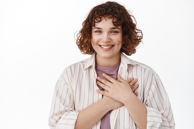 Kobieta z krótkimi kręconymi włosami, trzyma ręce na sercu i uśmiecha się zadowolona do kamery, dziękuje, docenia miły gest, jest wdzięczna, stoi na białym tle.