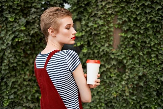Kobieta z krótkimi włosami jasny makijaż na zewnątrz pozuje modę