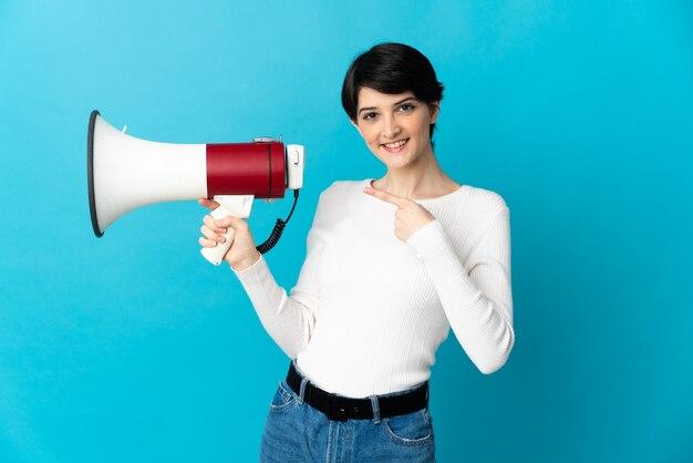 Kobieta z krótkimi włosami na odizolowanej ścianie trzyma megafon i wskazuje stronę