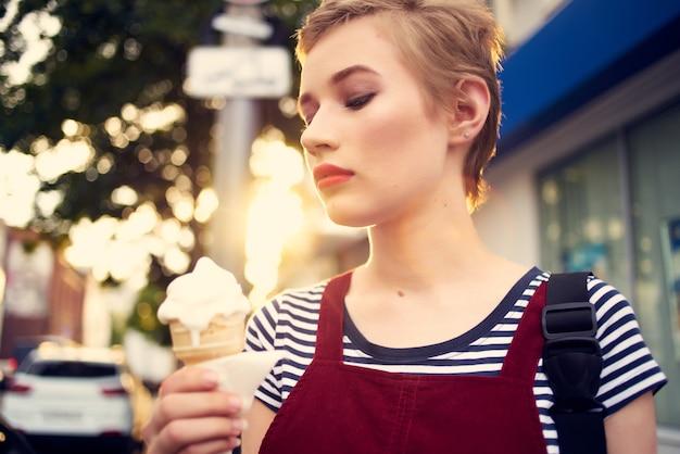 Kobieta z krótkimi włosami na ulicy jedząca lody spacer zabawy