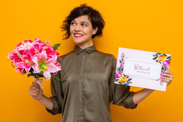 Kobieta z krótkimi włosami trzymająca kartkę z życzeniami i bukiet kwiatów szczęśliwa i wesoła uśmiechnięta z okazji międzynarodowego dnia kobiet 8 marca stojąca na pomarańczowym tle