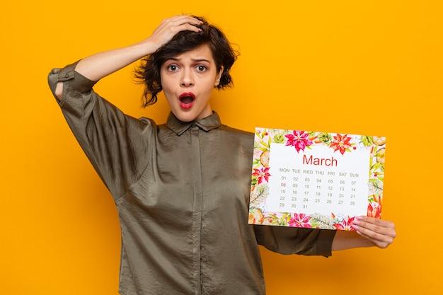 Kobieta z krótkimi włosami trzymająca papierowy kalendarz miesiąca marca patrząc na kamerę zdumiona i zdziwiona świętująca międzynarodowy dzień kobiet 8 marca stojąc na pomarańczowym tle