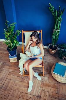 Kobieta z książką, siedząc w fotelu
