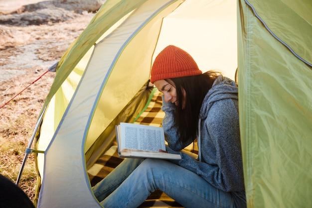 Kobieta z książką w namiocie. przycięty obraz.