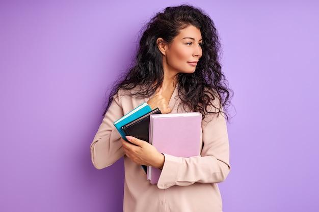 Kobieta z książkami na białym tle na fioletowej ścianie, miłość do edukacji, studia. studentka w bluzce