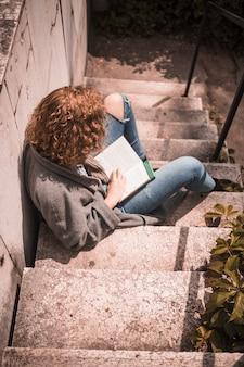 Kobieta z książkowym obsiadaniem na kamiennym schodku