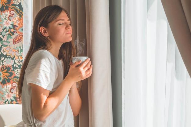 Kobieta z kubkiem gorącego napoju przy oknie. patrzę w okno i piję herbatę. dzień dobry z herbatą. jesień zima