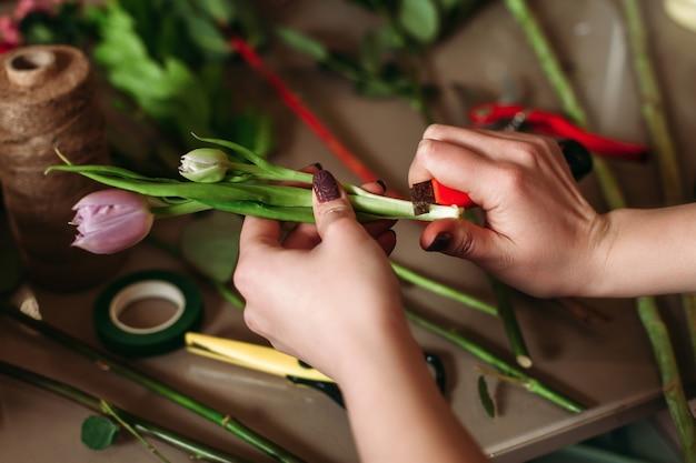 Kobieta z kwiatami nad stołem z narzędziami kwiaciarni.