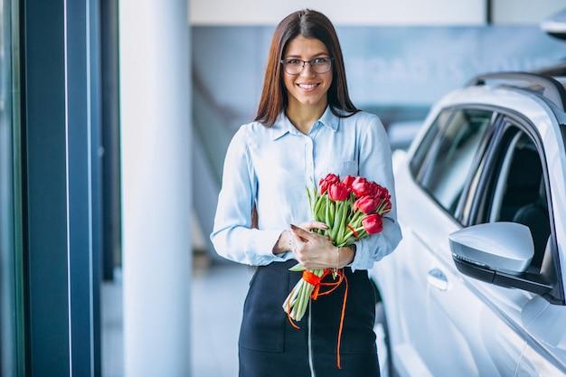 Kobieta z kwiatami w samochodowym salonie wystawowym