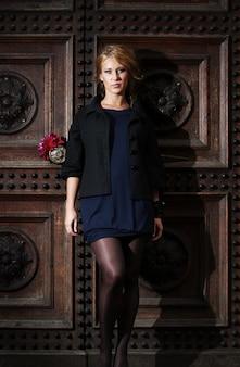 Kobieta z kwiatem obok drewnianego drzwi