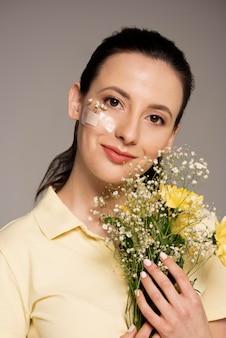 Kobieta z kwiatem pomocy zespołu na twarzy