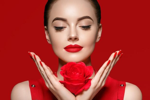 Kobieta z kwiatem róży. piękna kobieta portret z pięknymi paznokciami manicure róży i fryzurą salonową na czerwonym tle .