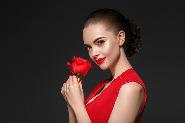 Kobieta z kwiatem róży. piękno portret kobiety z piękną fryzurę kwiat róży i salon na szarym tle. strzał studio.