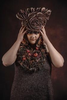 Kobieta z kwiecistym kapeluszem na ciemnym pokoju