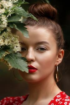 Kobieta z kwitnącym drzewem. letni makijaż na spacery. czerwona letnia sukienka