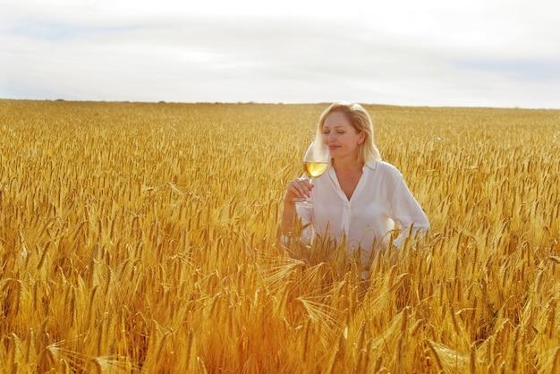 Kobieta z lampką wina w polu pszenicy