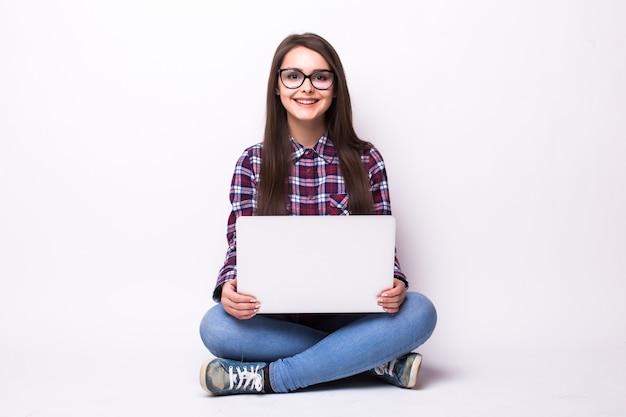 Kobieta z laptopa siedząc na podłodze. na białym tle.