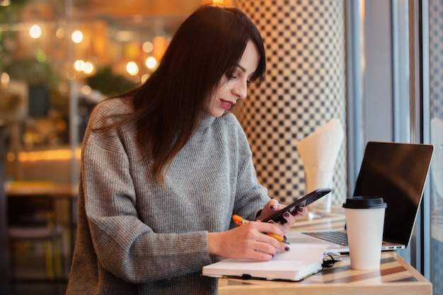 Kobieta z laptopem i telefonem komórkowym