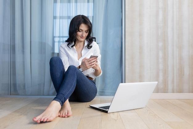 Kobieta z laptopem i telefonem pracuje w domu
