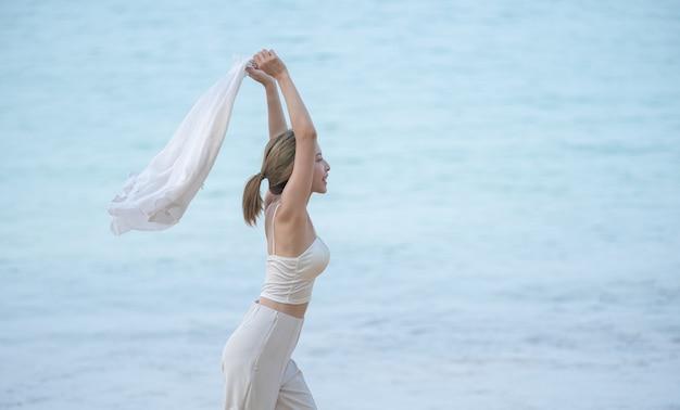 Kobieta z latającym szalikiem lub koszulą w ręce jogging na plaży oceanu. ciesz się latem.
