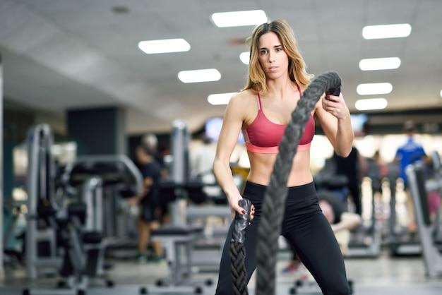 Kobieta z liny bitwy ćwiczeń w siłowni fitness.