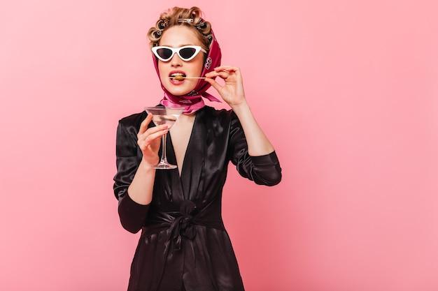 Kobieta z lokami ubrana w czarną sukienkę gryzie oliwkę i trzyma martini na różowej ścianie