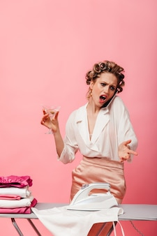 Kobieta z lokówki rozmawia z oburzeniem przez telefon i trzyma kieliszek martini