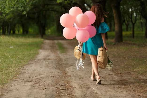 Kobieta z łozinowym koszem, kapeluszem, różowymi balonami i kwiatami chodzi na wiejskiej drodze