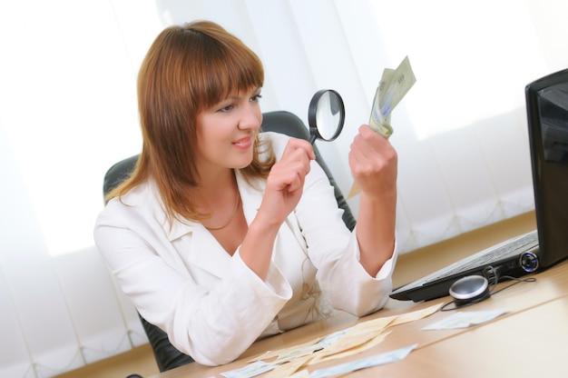 Kobieta z lupą w dłoniach weryfikuje autentyczność rachunku. kalkulator, gotówka przy biurku. jasne tło