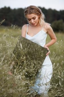 Kobieta z lustrem w ręku w polu o zachodzie słońca