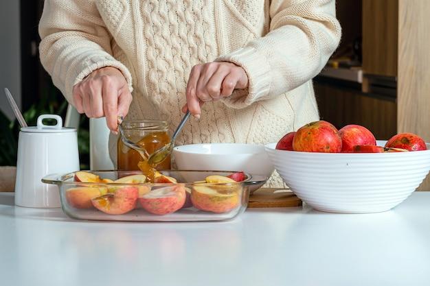 Kobieta z łyżką wylewanie jabłek z miodem w szklanym pojemniku i przygotowywanie ich do gotowania, koncepcja domowej roboty pieczenia pustyni
