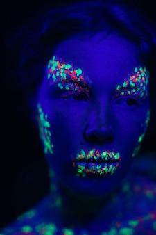 Kobieta z makijażem fluorescencyjnym, którzy szukają drogi