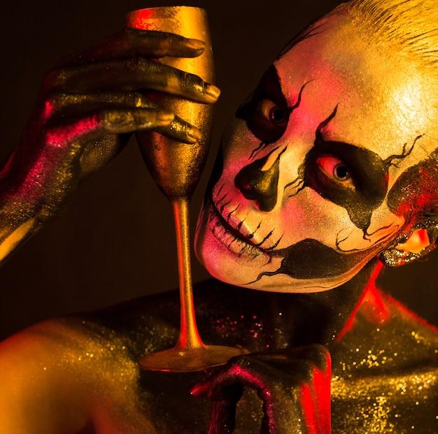 Kobieta z makijażem szkielet trzyma szkło
