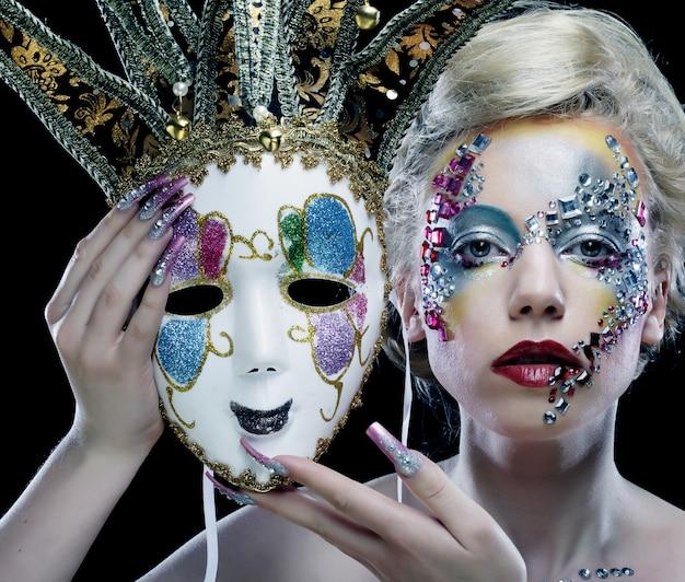 Kobieta z makijażu artystycznego gospodarstwa maska