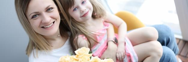 Kobieta z małą dziewczynką na kolanach trzymając bukiet kwiatów. koncepcja dzień matki