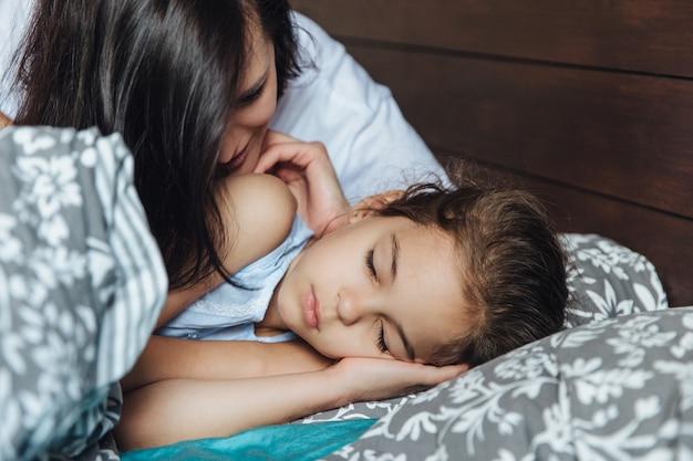 Kobieta z małą sypialną dziewczyną w łóżku