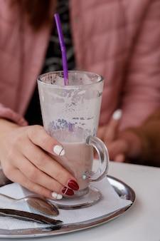 Kobieta z malującymi różowymi gwoździami i kurtką trzyma gorącą cappuccino filiżankę