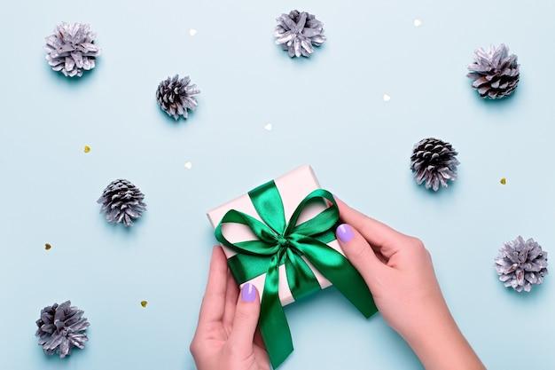 Kobieta z manicure trzyma zielone pudełko lub owinięty prezent na niebieskim tle z malowanymi srebrnymi szyszkami i złotym konfetti. prezenty świąteczne lub koncepcja zakupów. widok z góry