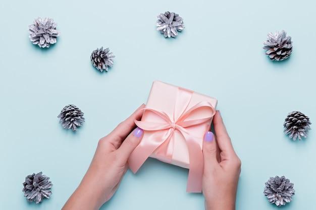 Kobieta z manicure trzyma zielone pudełko lub owinięty prezent na niebieskim tle z malowanymi srebrnymi szyszkami i złotym konfetti. prezenty świąteczne lub koncepcja zakupy w drugi dzień świąt bożego narodzenia. widok z góry