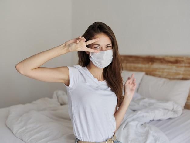 Kobieta z maseczką medyczną na twarzy trzyma dwa palce przy oczach w jasnym pokoju