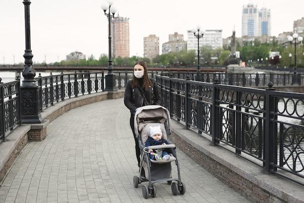 Kobieta z maską chroniącą przed koronawirusem, covid-19 pcha wózek na ulicy