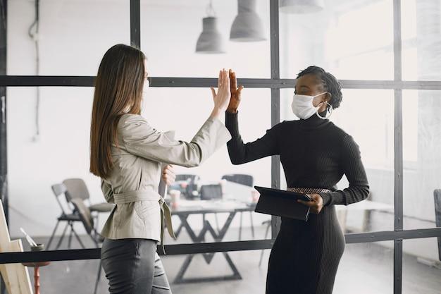 Kobieta z maską do twarzy w pracy z papierami. udana firma, praca zespołowa.