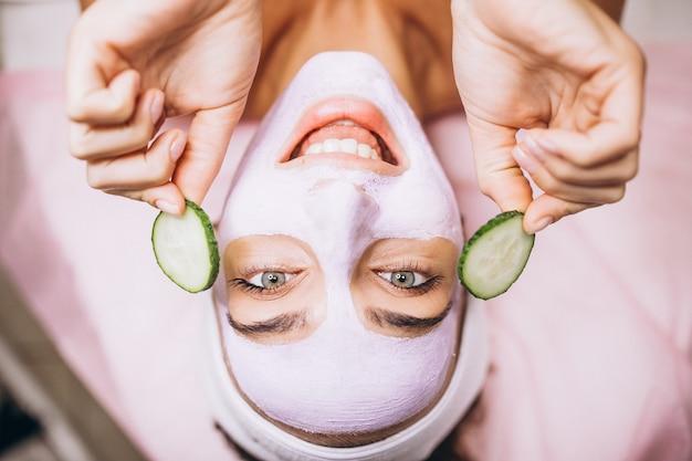 Kobieta z maską i ogórkiem na ona oczy