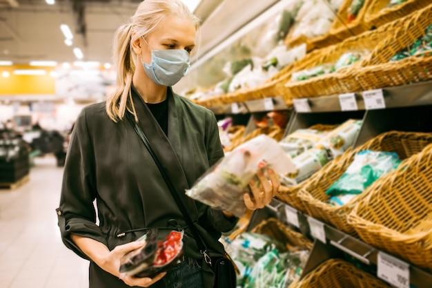 Kobieta z maską kupuje artykuły spożywcze w supermarkecie podczas pandemii