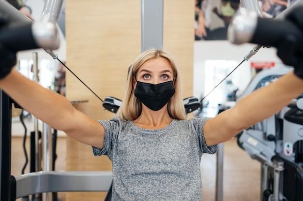 Kobieta z maską medyczną i rękawiczkami, trening na siłowni